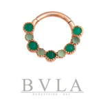 a gold septum ring with green gems